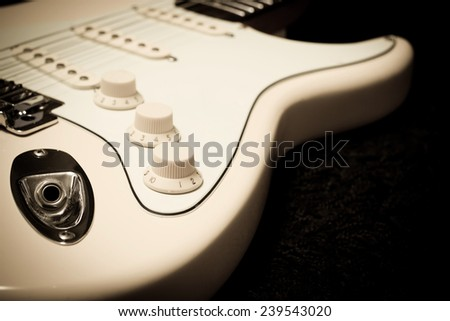 part of mastic electric guitar on black , shallow dept of field & focus to knob for music background - stock photo