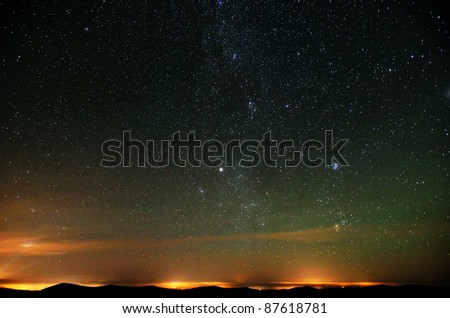 Part of Milky way over city lights and mountains natural photo - stock photo