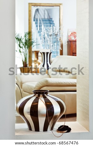 Part of modern art deco style drawing-room interior with striped vase - stock photo