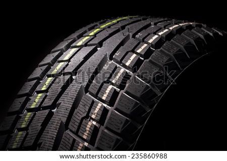 Part of modern non-studded winter tire against black background, studio shot - stock photo