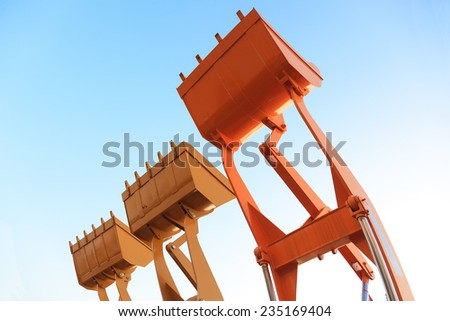 Part of  modern yellow excavator machines,the buckets/shovels raised against blue sky in a construction site. - stock photo