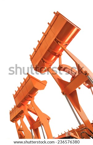 Part of  modern yellow excavator machines,the buckets/shovels raised against  sky in a construction site. - stock photo