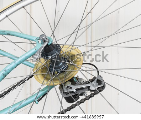 Part of old bicycle wheel, derailleur, and chain