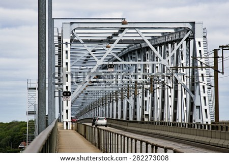 Part of Old Littlebelt Bridge with cars and catenary wires - stock photo