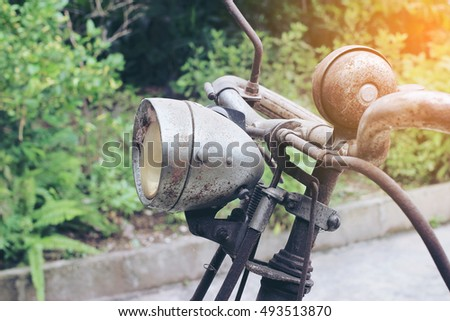 Part of old vintage bike with headlights and rear view mirror in the garden with green background.
