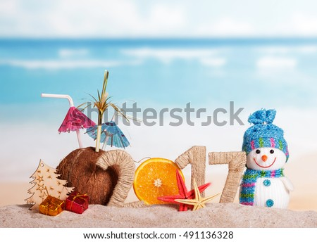 Part of orange instead of the number 0 in the amount of 2017, coconut snowman, Christmas tree, Christmas gifts and starfish in the sand against the sea.