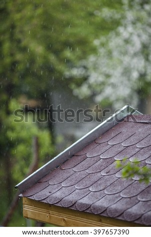 Part of red bitumen tiles roof under the rainy day - stock photo