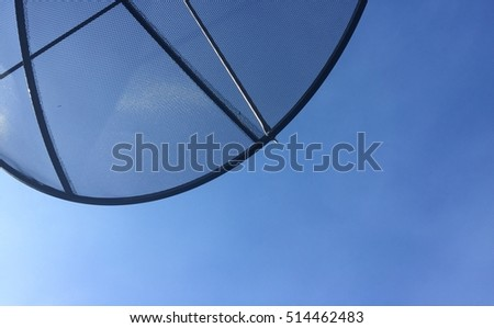 Part of satellite dish and blue sky with copyspace