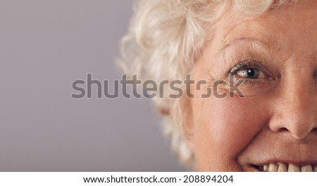 Part of senior woman face with focus on grey eyes. Old woman face close-up with copy space on against grey background. - stock photo