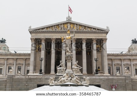 Part of the Austrian Parliament building during the day in the winter with the Austrian Flag at the top. The Goddess Athena Statue can be seen at the front.