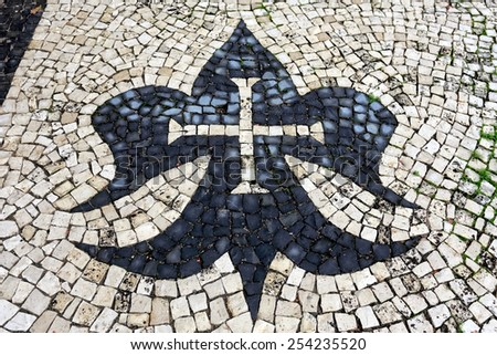 Part of the backyard floor of a northern church in Portugal with christian symbols. Portuguese pavement style, a traditional-style pavement used in pedestrian areas in Portugal and Brazil - stock photo