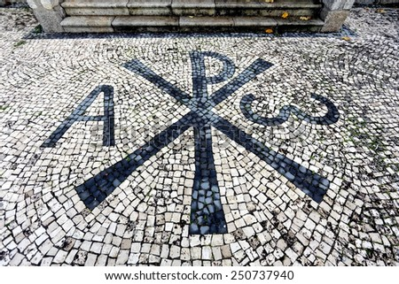 Part of the backyard of a northern church in Portugal with christian symbols. Portuguese pavement style, a traditional-style pavement used in pedestrian areas in Portugal and Brazil - stock photo