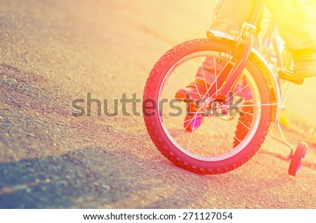 Part of the children's bicycles and child on the background of the asphalt when it is backlit. Vintage composition