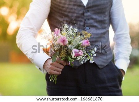 Part of the groom holding wedding bouquet in hand