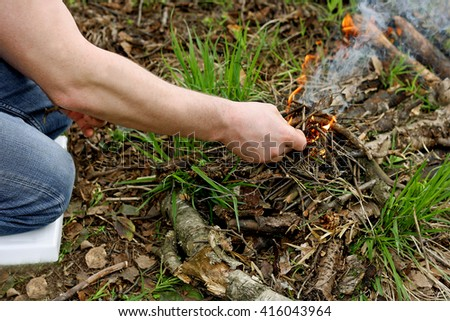 Part of the image of the man who sits on his knees in the forest among the dry withered leaves. A man lighting a fire. - stock photo