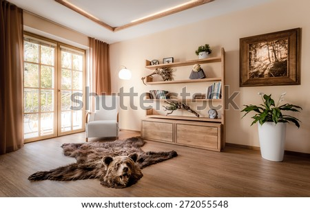 Part of the living room with the balcony doors bathed in the rays of the summer sun. The interior is decorated mostly with wooden features and hunting trophies. The room has a very warm feel. - stock photo