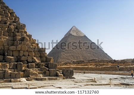 Part of the masonry of the pyramid of Cheops Pyramid of Khafre in the background. - stock photo