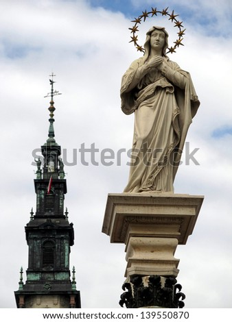 part of the monastery of Jasna Gora in Czestochowa and the statue of Our Lady of the Immaculate Conception in front of the monastery - stock photo