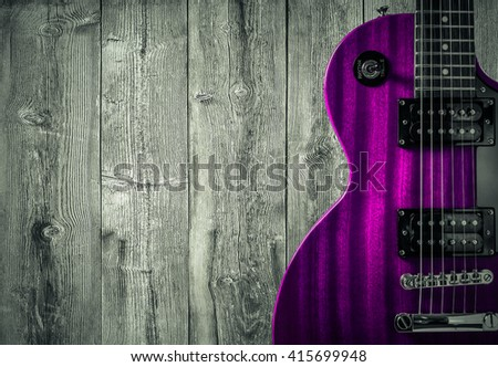Part of the pink electric guitar on wooden background. A place for writing of the text - stock photo