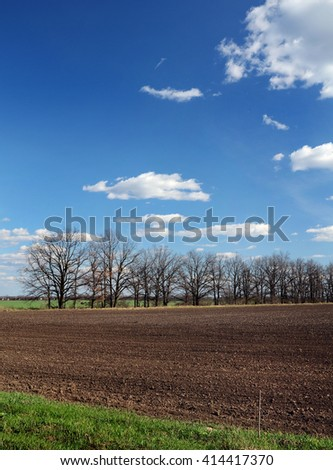 part of the plowed field in the spring, blue sky - stock photo