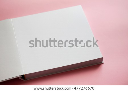 Part of white empty open book on pink background