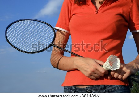 Part of woman body with a racket, shuttlecock in her hands - stock photo