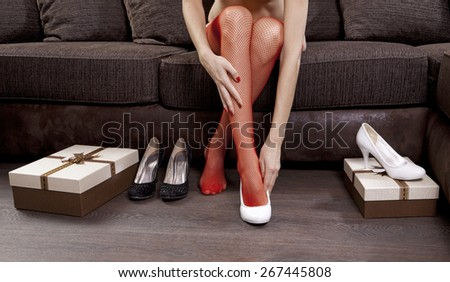 part of woman trying on several shoes in the mall - stock photo