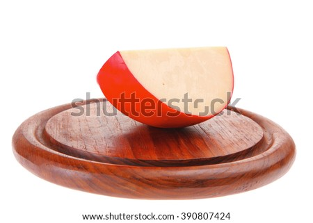 part of yellow cheese on dark wooden plate - stock photo
