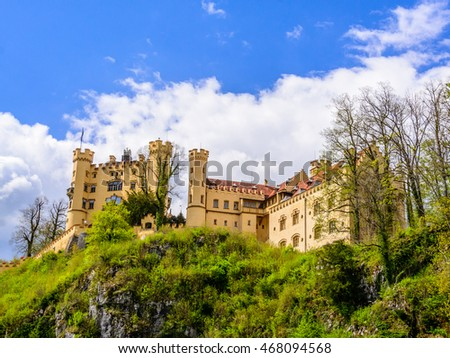 Part view from below to world-famous Hohenschwangau Castle (Schloss) on the cliff under blue sky with clouds, Fussen, Bavaria, Germany