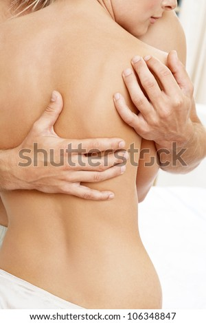 Part view of a man's hands caressing a woman's bare back.