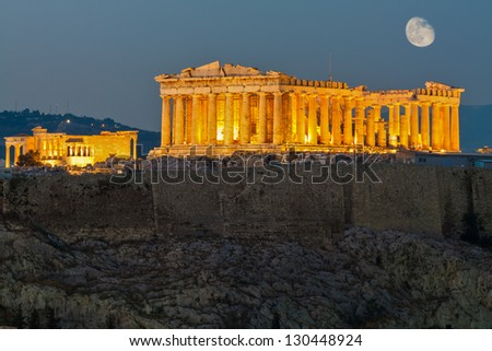 Parthenon construction in Acropolis Hill in Athens, Greece shot in blue hour with moon in the sky