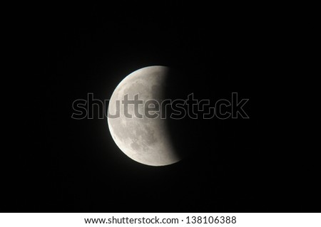 partial moon eclipse in the night in winter - stock photo