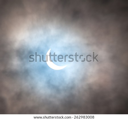 Partial Solar Eclipse of the Sun.The eclipse it partly obscured by the clouds - stock photo