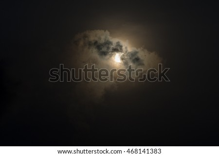 partial solar eclipse with dark clouds