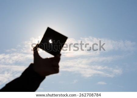 Partial Sun eclipse. Man covering a strong sunlight by dark plate and shows sun eclipse. man hand silhouette on blue sky. - stock photo