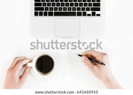 Partial top view of person holding cup of coffee and writing on blank paper at workplace with laptop, wireless communication concept