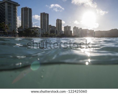Partial underwater shot of Waikiki Hawaii resorts and Diamond Head Peak shortly after sunrise. - stock photo