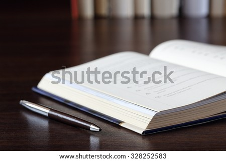 Partial View of A Book and a Pen on Wooden Deck, illustrating Concept of Research Work and Learning Process