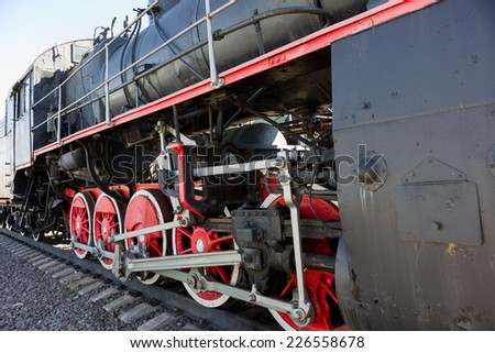 Partial view of a steam locomotive. Black metal boiler, red wheels, link motion, rods and drives, engineer's cab - stock photo