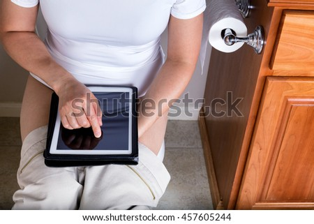 Partial view of a women using wireless internet device while sitting on the toilet. Selective focus on her index finger.  - stock photo