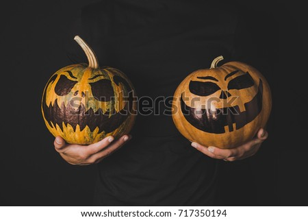 partial view of man with pumpkins with scary faces in hands isolated on black
