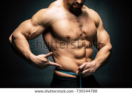 partial view of shirtless sportive man measuring body with measuring tape isolated on black