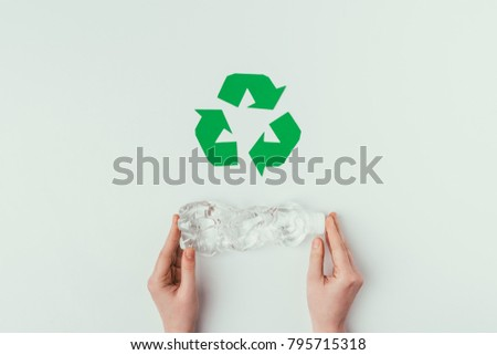 partial view of woman holding plastic bottle with recycle sign isolated on grey