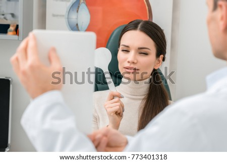partial view of young woman getting eye test by oculist in clinic