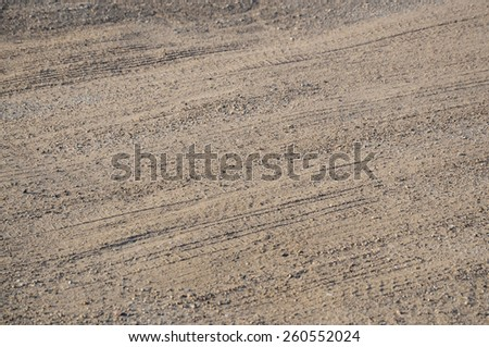 Partially covered with sand asphalt road. Close up.