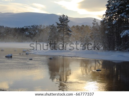 Partially frozen lake. (Loch Morlich, Scotland, which is situated in the Cairngorm National Park.) - stock photo