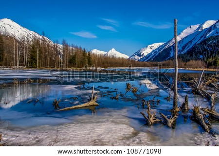 Partially Frozen Lake with Mountain Range Reflected in the Great Alaskan Wilderness.  A Beautiful Landscape of Blue Sky, Trees, Rock, Snow, Water and Ice.  Near Seward highway near Anchorage, Alaska. - stock photo
