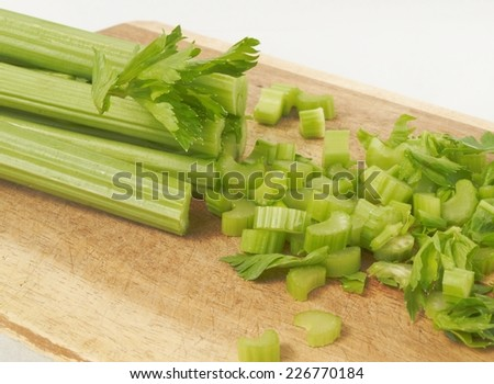 Partially sliced ??celery on a wooden cutting board  - stock photo