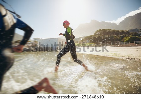 Participants running into the water for start of a triathlon. Two triathletes rushing into water. - stock photo