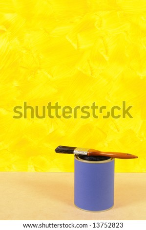 Partly finished blank yellow painted wall with paint can and paintbrush.  Space for copy. - stock photo